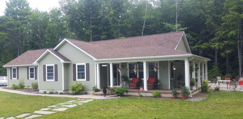 a light green ranch-style home with a wraparound porch and a patio in back