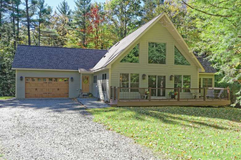 a chalet style home with several windows and sliding doors, a front porch and an attached garage