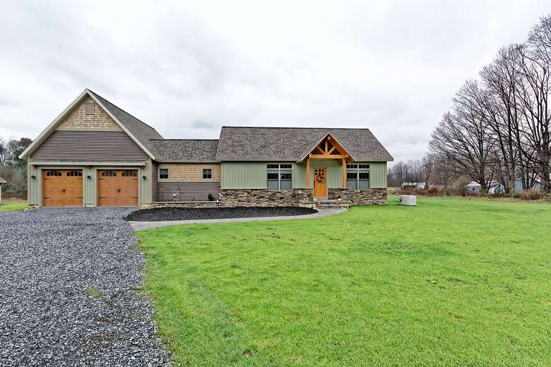 a ranch style home with stone trim, attached garage with stained wood garage doors and stained wood front porch