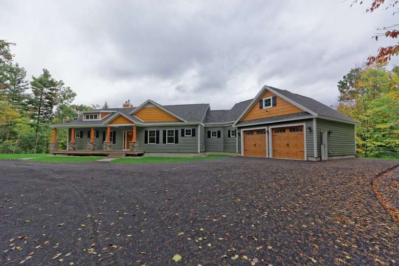 a modern yet rustic looking home that combines vinyl siding, with wood paneled garage doors, wood accents in the peaks and dormers, and wood and stone columns on the front entrance