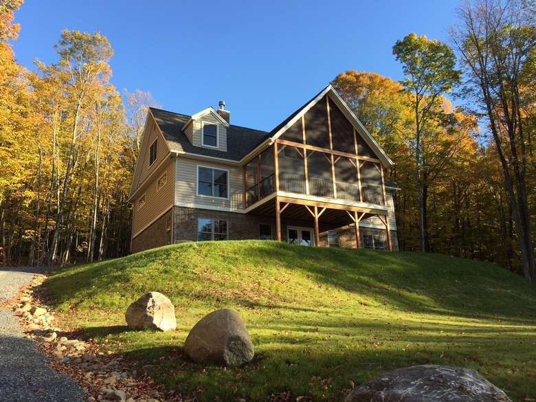a large multi-story home on hilltop lot, with a strikingly designed, large screened in porch in front