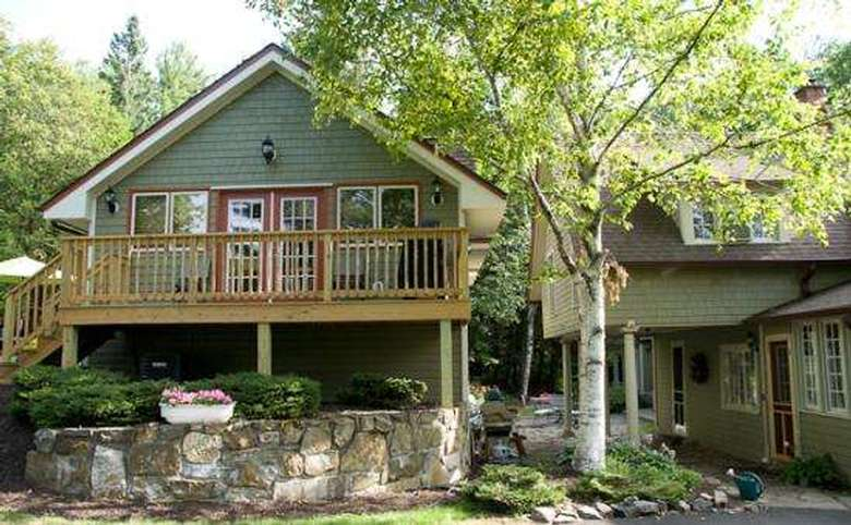 green carriage house with a wooden porch on the front