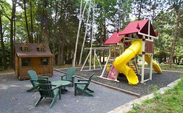kids playground with a large yellow slide, swingset, and green adirondack chairs