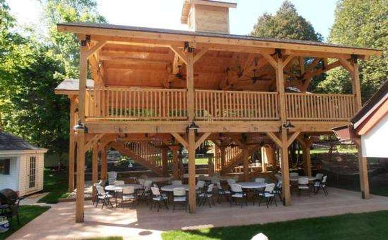 large two-story wooden structure with tables and chairs set up for an event on the first floor