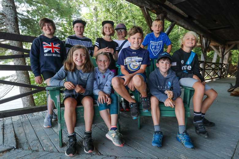 small group of young campers posing for a group photo around green chairs