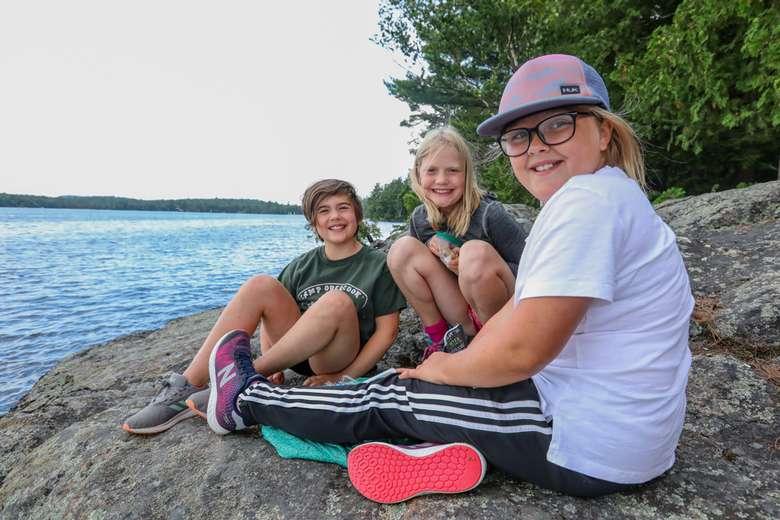 three girls sitting on a rocky shoreline by a lake