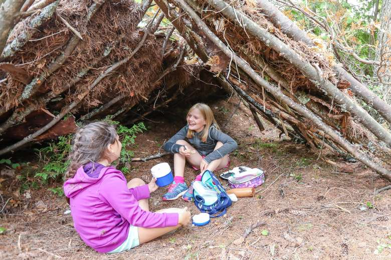 two girls under a tent made out of sticks and brush