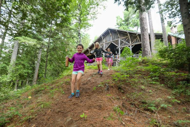 three girls walking down a hill from a camp building