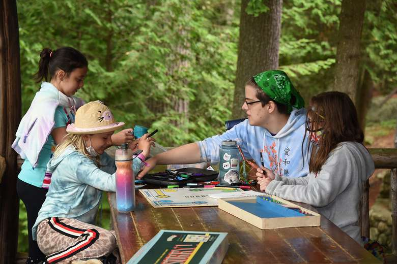 Three campers and a counselor are around a wooden table playing board games on an outdoor porch.
