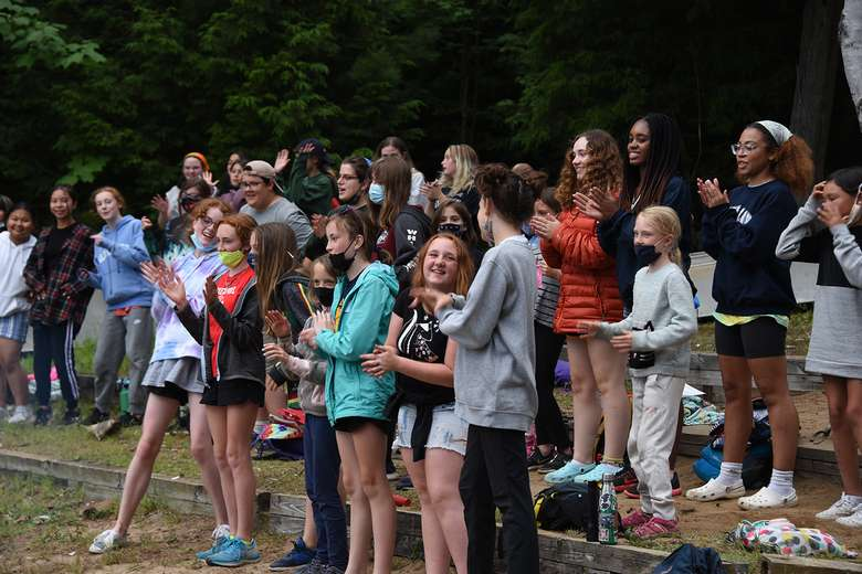 Campers standing singing and clapping on a beachfront during a campfire.