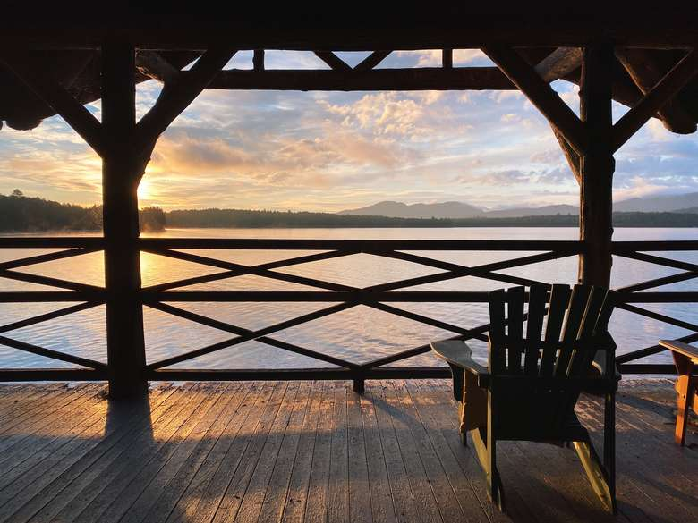In the background the sun rises over the mountains and Upper Saranac lake. In the foreground is the silhouette of a wooden structure in traditional Adirondack Great Camp Architecture and an Adirondack Chair on a deck.