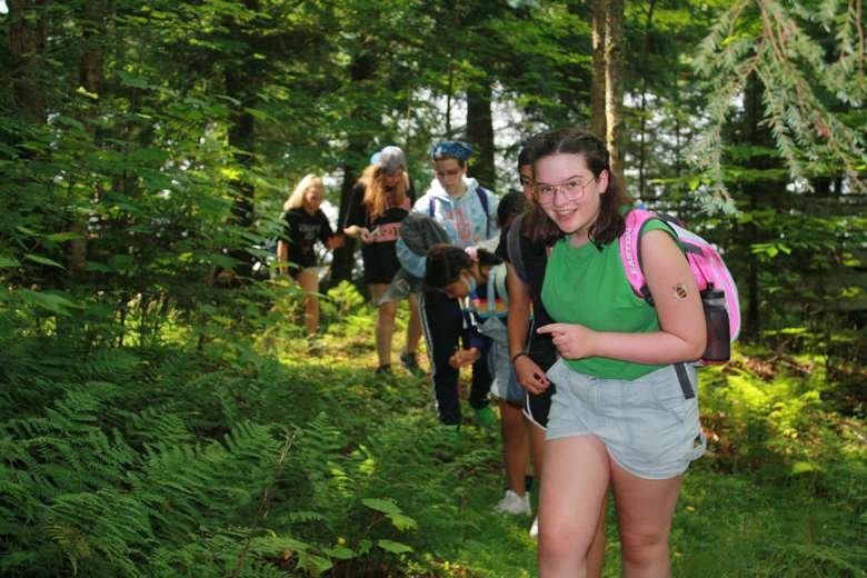 Campers on a trail on a nature hike. A young girl in the foreground wearing a bright pink backpack smiles and points to the lush ferns surrounding the path.