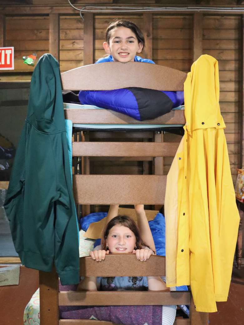 Two campers smile and peer through the slats of bunkbeds, one in the bottom bunk one in the top.