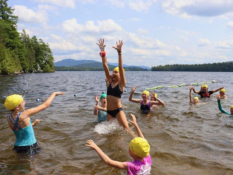 Young campers in waste deep water throw a ball to each other and jump to catch it as they play games during free swim on Upper Saranac Lake. The sky is bright blue with puffy white clouds and mountains are in the distance.