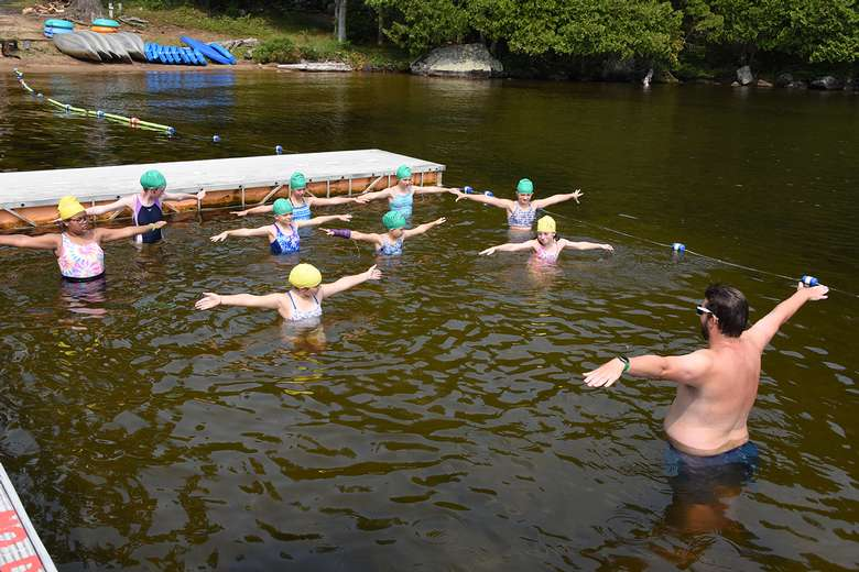 Campers in waist deep water reach out their arms to the sides to mimic the swim instructor standing at the front of the group teaching them a swimming stroke.