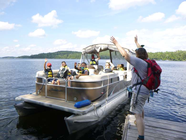A boat full of campers on a pontoon boat on Upper Saranac Lake wave as the camp nurse waves back from the dock
