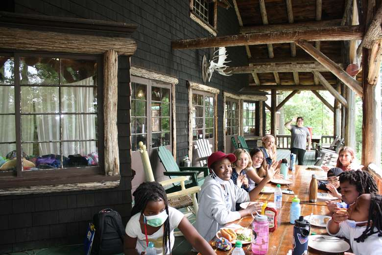 Campers eat lunch at a long table on the front porch of a rustic Adirondack Lodge. A counselor smiles and waves in the background.