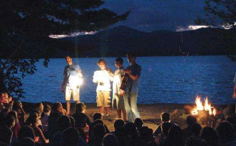 four people with flashlights standing in front of a group at dusk. lake george is visible in the background