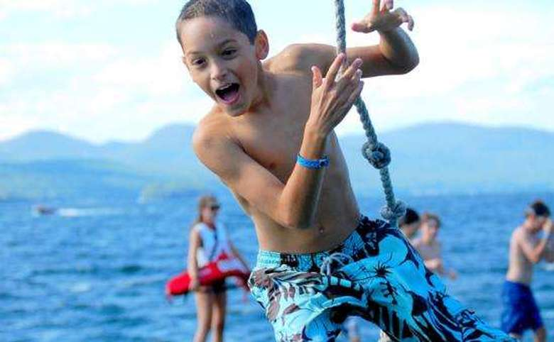 boy jumping off a rope swing into lake george