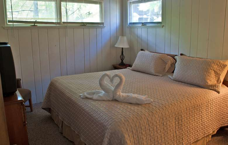 two towels forming swans forming a heart on a bed