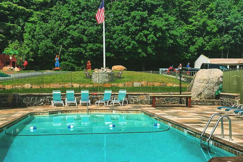 an outdoor pool with chairs near it and an American flag in the background on a flagpole