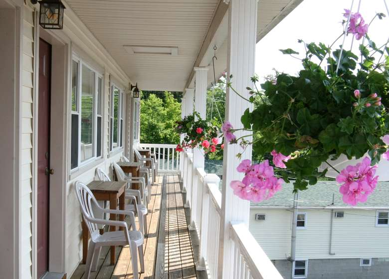 chairs and side tables on a porch with floral hanging baskets