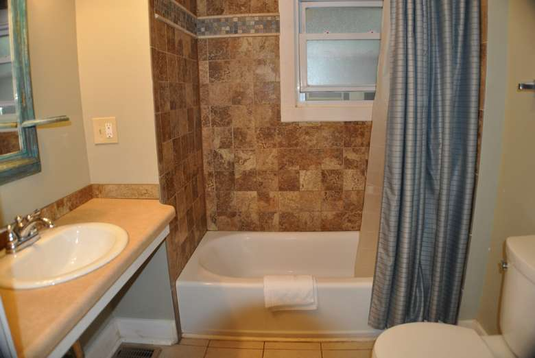 bathroom sink, tub with tile surround, blue shower curtain