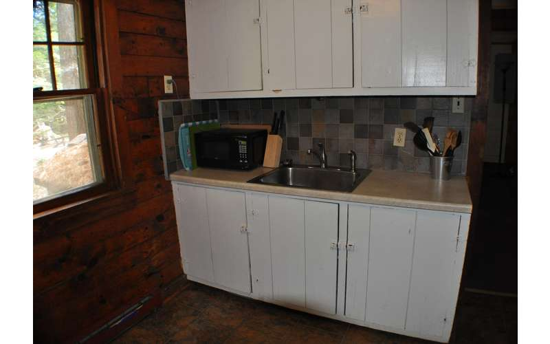 kitchen cabinets and sink with microwave