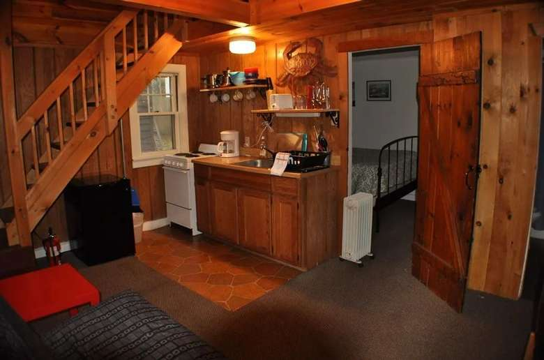 a small kitchen area inside a cottage near a bedroom entrance