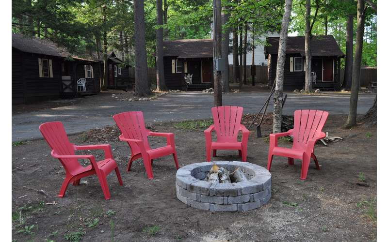 four red Adirondack chairs around a camp fire pit