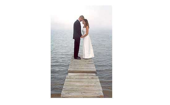 Couple at the end of a  dock staring into each other's eyes
