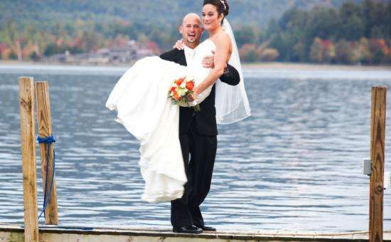 Man holding woman on dock in wedding attire