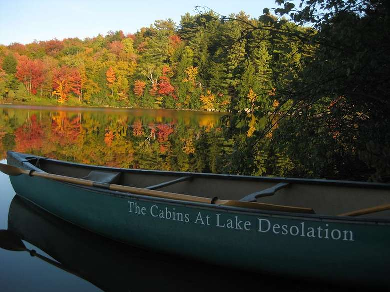 a green canoe on the water with fall foliage in the background