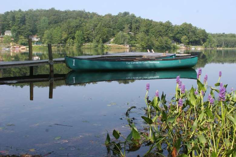 a green canoe at a dock on a lake