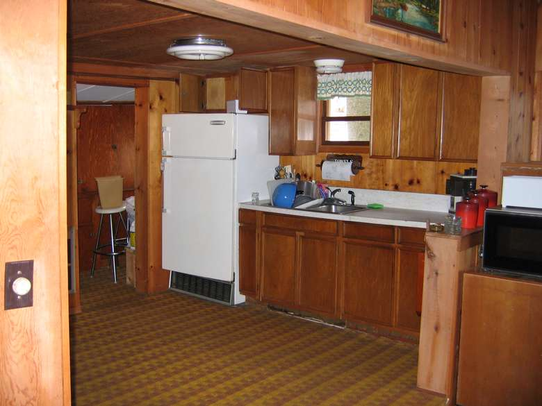 a kitchen with a white fridge, a sink, and a black microwave