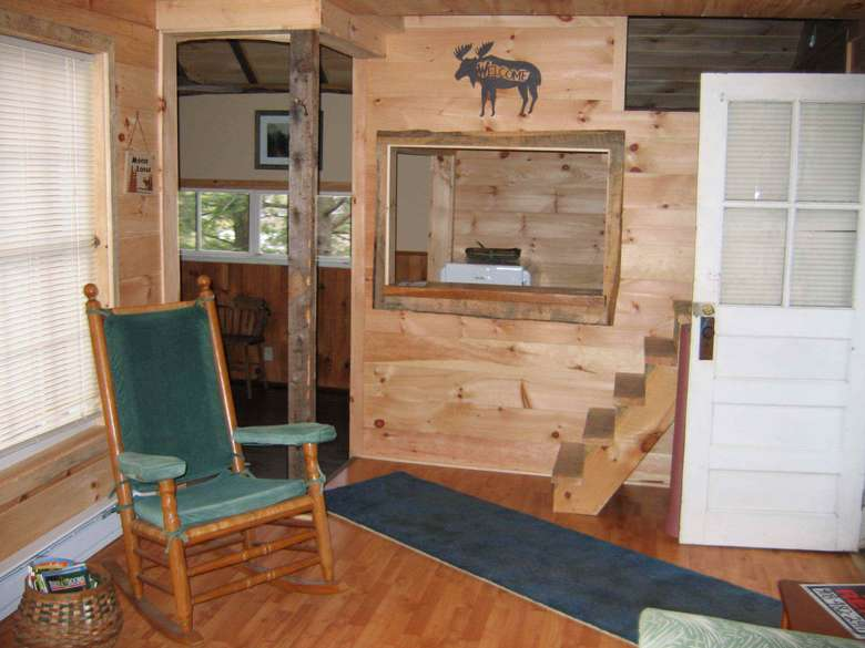 the front entrance of a cabin with a green chair and stairs behind the door