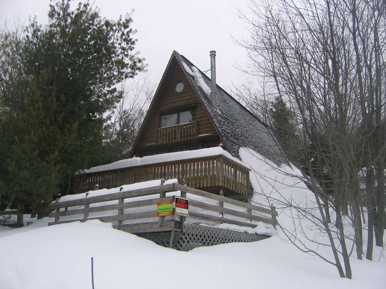 a large brown chalet with a triangular roof in the winter and covered in snow