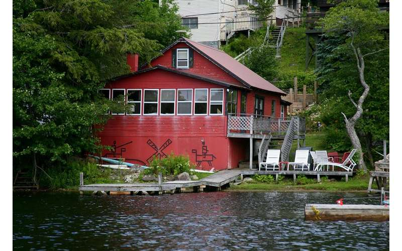 a large red cabin on the lake with a boat dock
