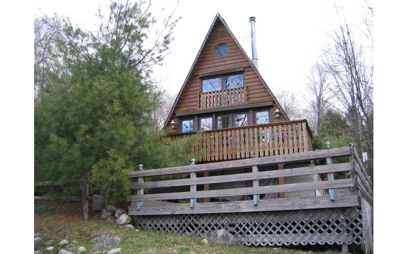 a large wooden chalet with a triangular roof and front deck