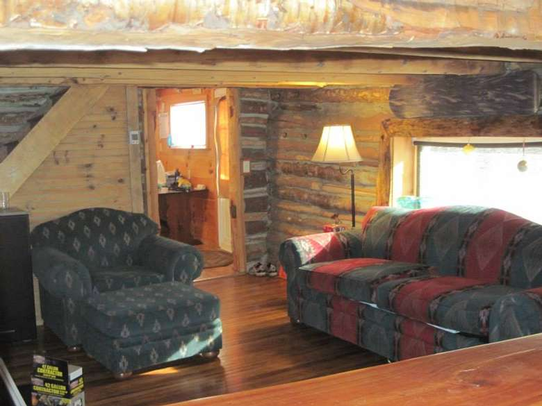 a rustic living room with wooden walls, a sofa, and a chair