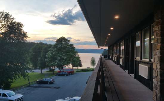 a view of the lake from the porch along hotel rooms