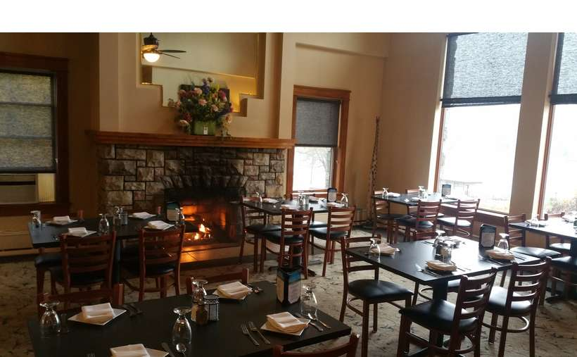 a spacious dining room at a restaurant with many square tables and a fireplace in the back