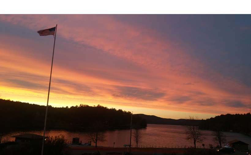 a sunset over a lake with a flagpole high in the sky