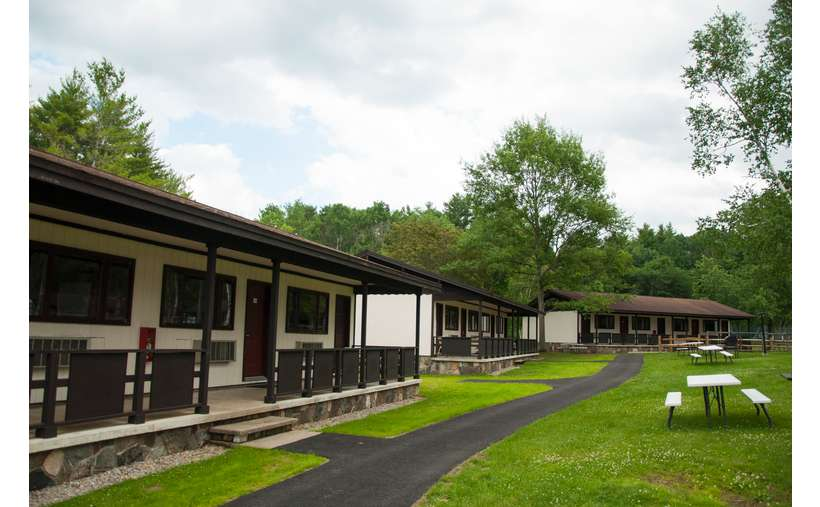 multiple separate cabins on a grassy lawn at a hotel