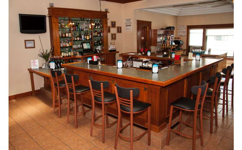 a rectangular bar with seating and drinks in the back