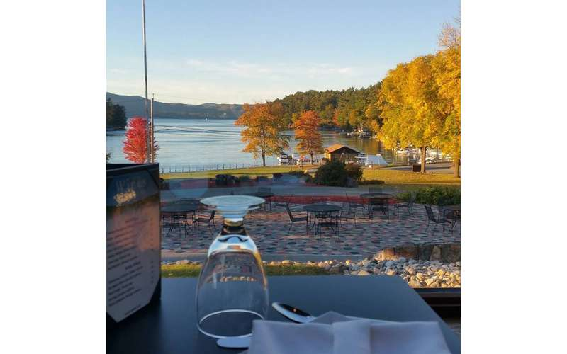 fall foliage around a lake while viewing from a patio