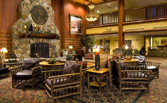 lobby of six flags great escape lodge with rustic furniture and a large stone fireplace