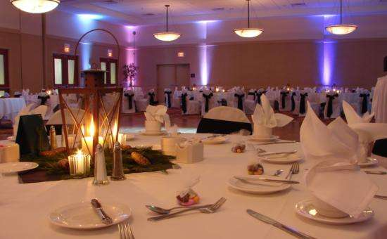 hotel ballroom set for a wedding with white tablecloths and chair covers