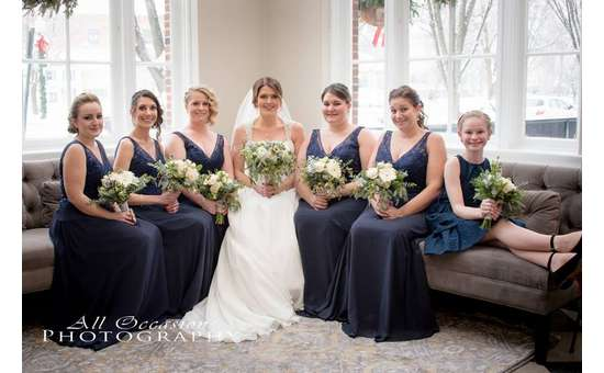 Bridesmaids and bride sitting along a bent couch