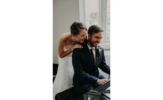 Groom playing piano and bride holding his shoulders